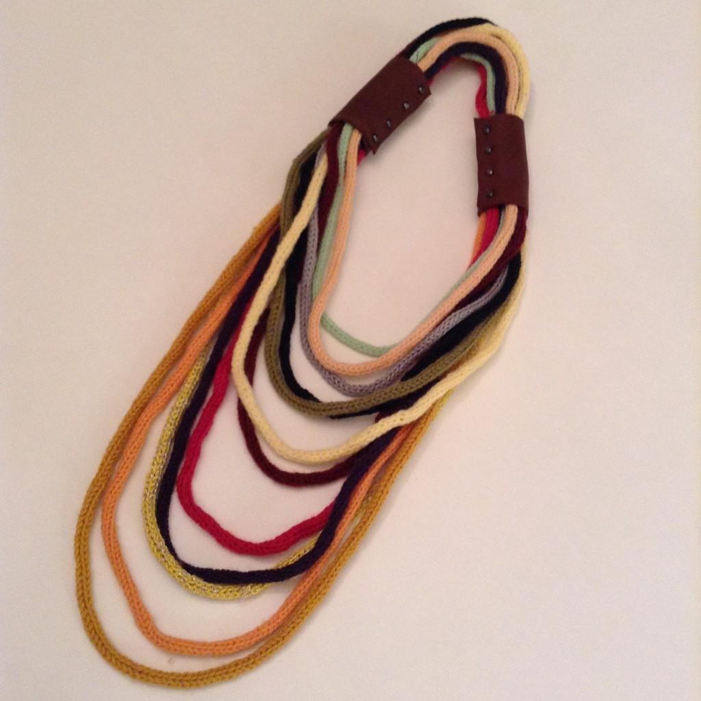 Halsschmuck aus langen bunten Wollschnüren mit Lederbesätzen